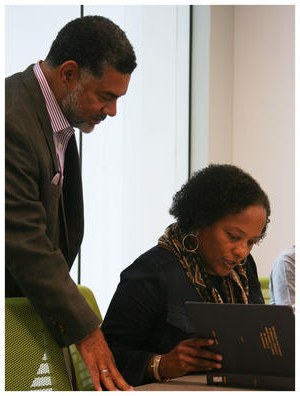 Alicia Dixon (sitting) 和 Board member Biff Clark look at Dr. Foster's thesis. It's the first time the institute viewed it.